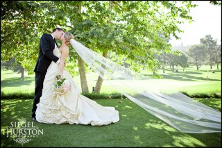romantic wedding photography with a long veil blowing in the wind