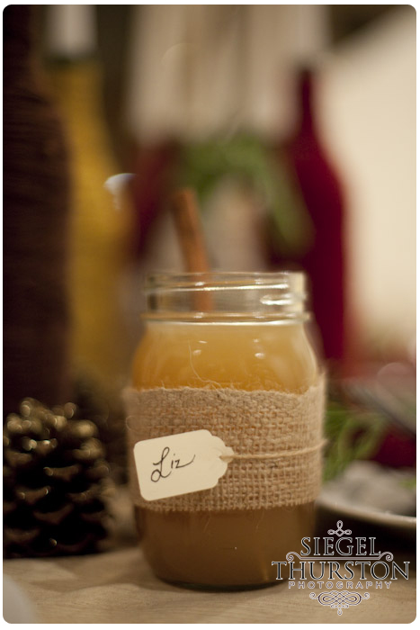 mason jar full of apple cider decorated with burlap twine and a personal name tag