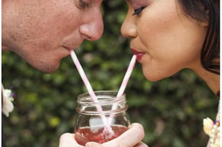 bride and groom sharing a pink lemonade through pink and white striped straws