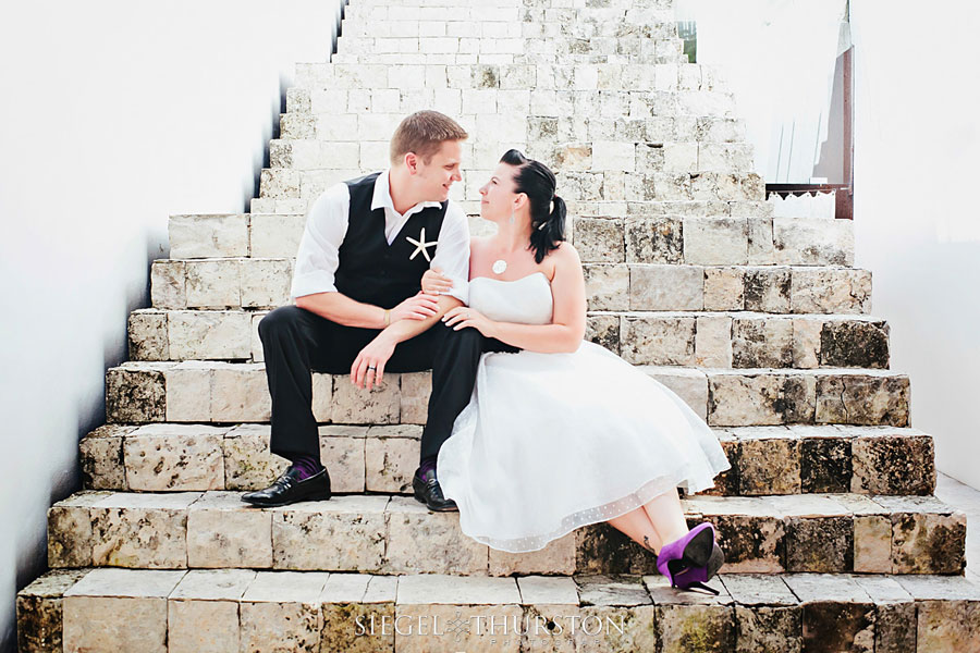 trash the dress playa del carmen evan and meagan sitting on stone steps in a cute authentic mexican village